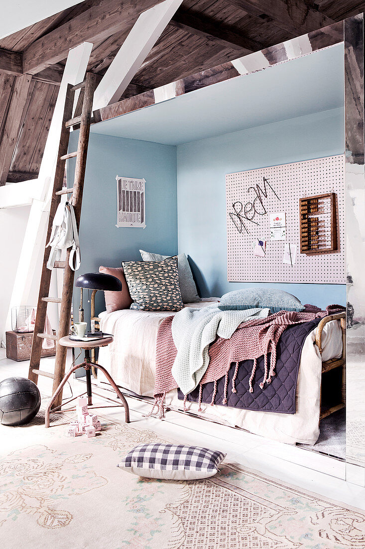 Bed in niche in rustic bedroom in pastel shades