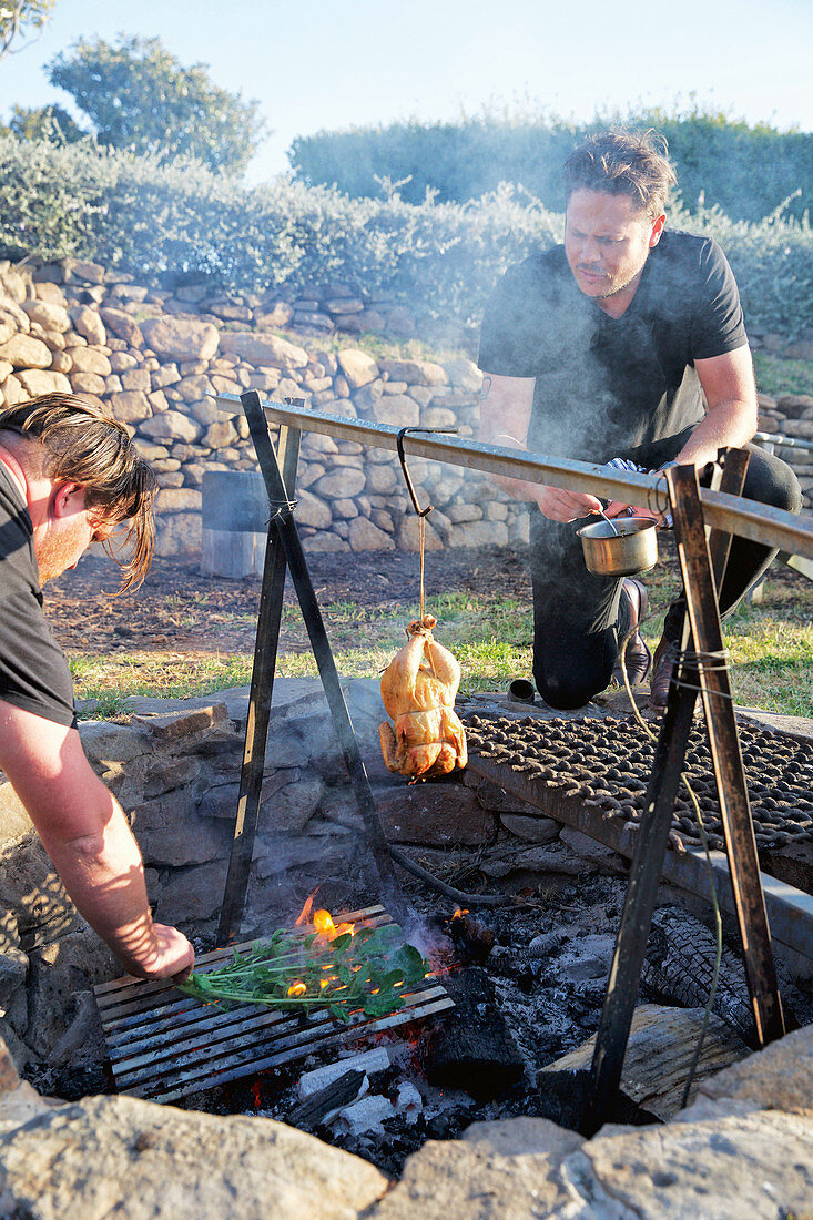 Roast chicken hanging in smoke above rustic barbecue pit