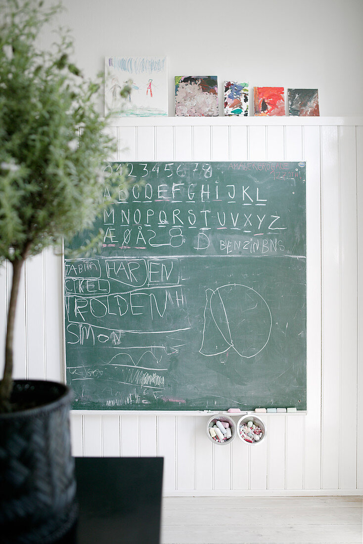 Chalkboard and children's pictures on wood-clad wall