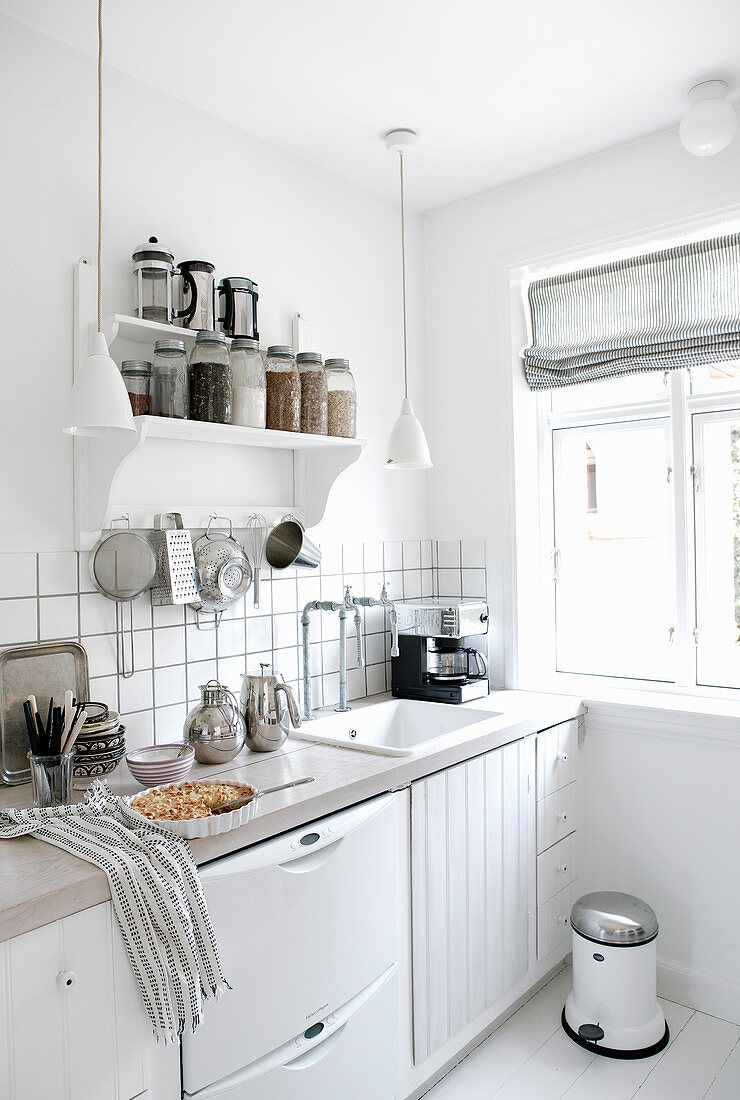 Groceries on shelves in white kitchen