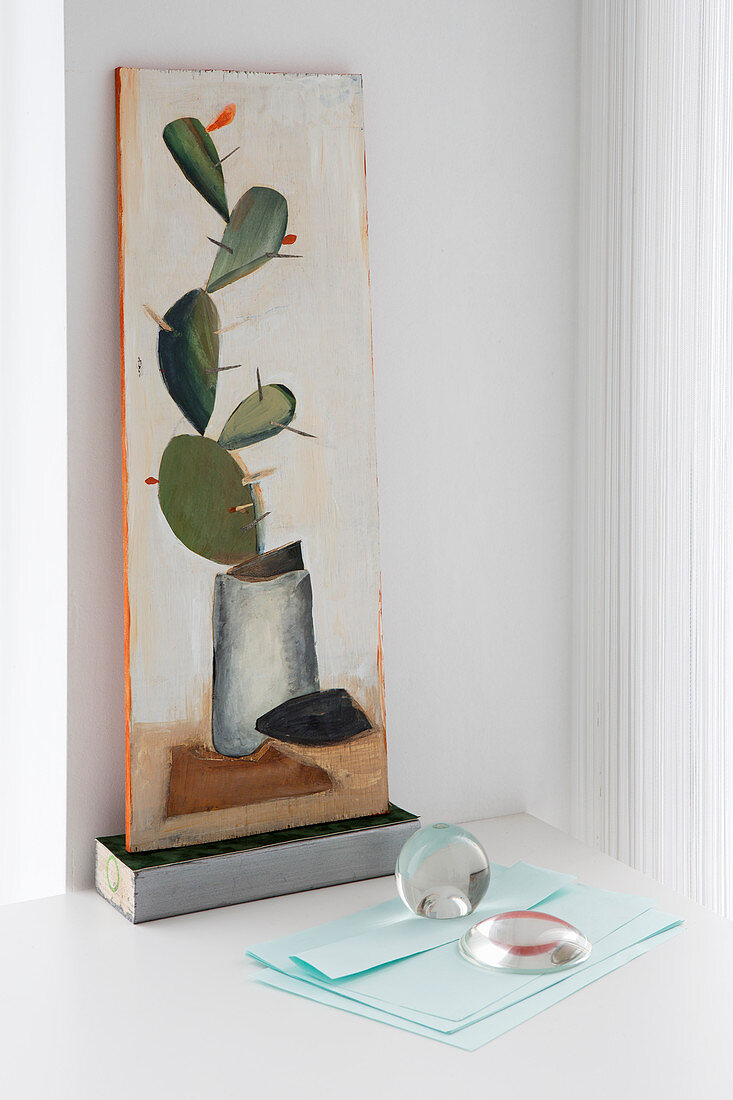 Glass paperweights on pale blue paper below picture of cactus