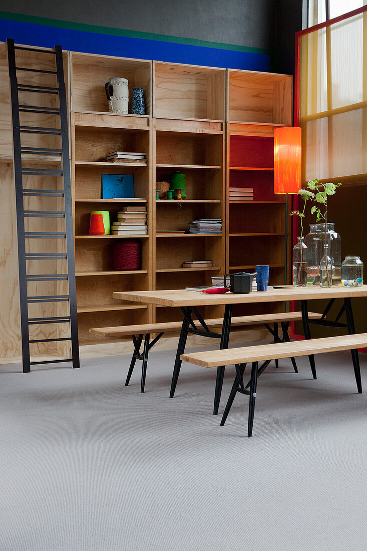 Dining table and benches in front of shelves with library ladder in high-ceilinged room