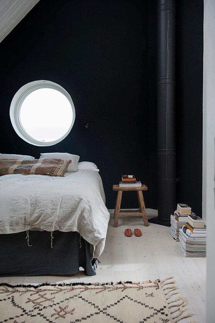 Bed below round window in black bedroom wall