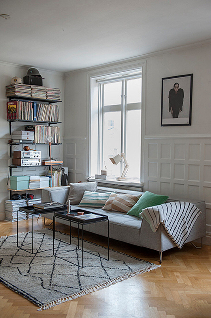Slimline coffee tables and modern sofa against panelled wainscot