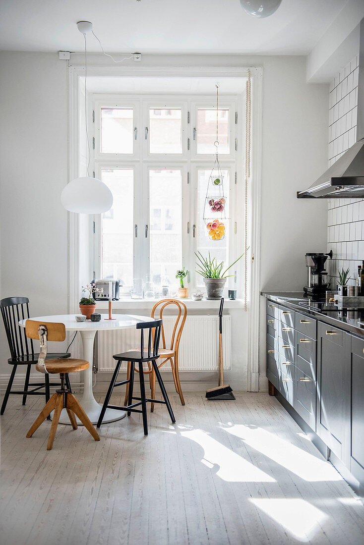 Various chairs around round designer table in kitchen-dining room