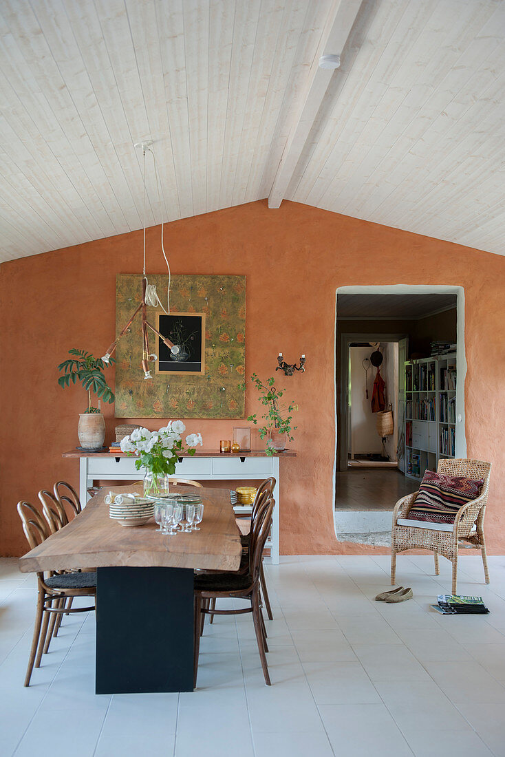 Rustic dining table in front of terracotta-coloured wall