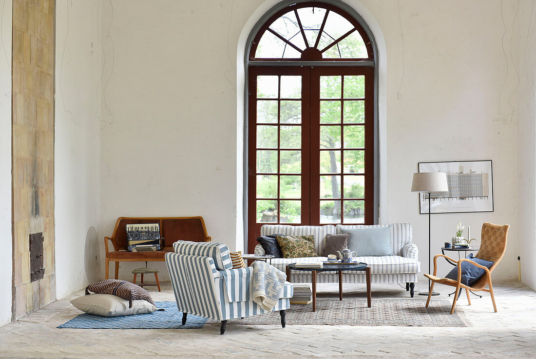 Large arched window in living room with high ceiling