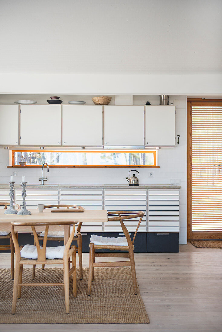 Classic chairs in dining area in front of pale fitted kitchen