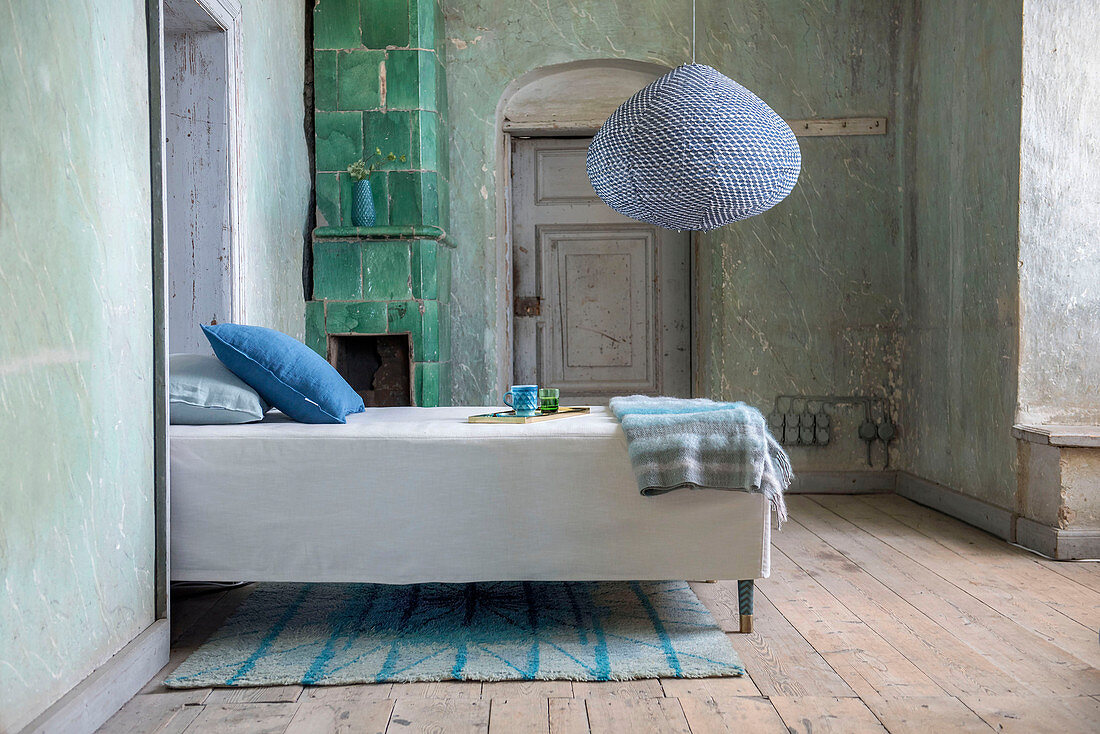 Bed in front of green-tiled stove in bedroom