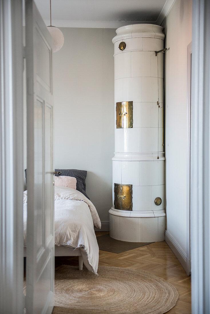 Round, Swedish tiled stove in bedroom