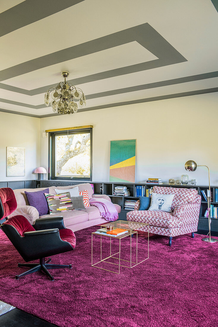 Upholstered furnishings and rug in shades of pink and purple in living room