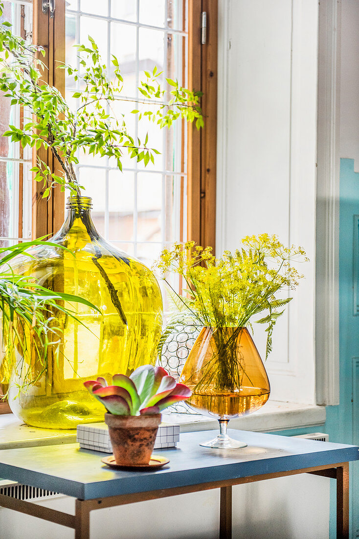 Demijohn and large amber glass used as vases in front of window