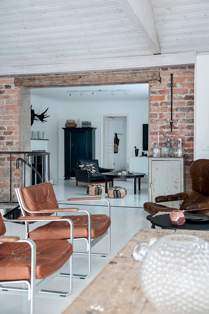 Leather armchairs in living room with brick wall and white floor