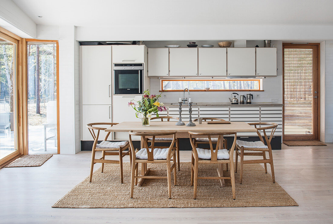 Wishbone Chairs around dining table in front of grey fitted kitchen