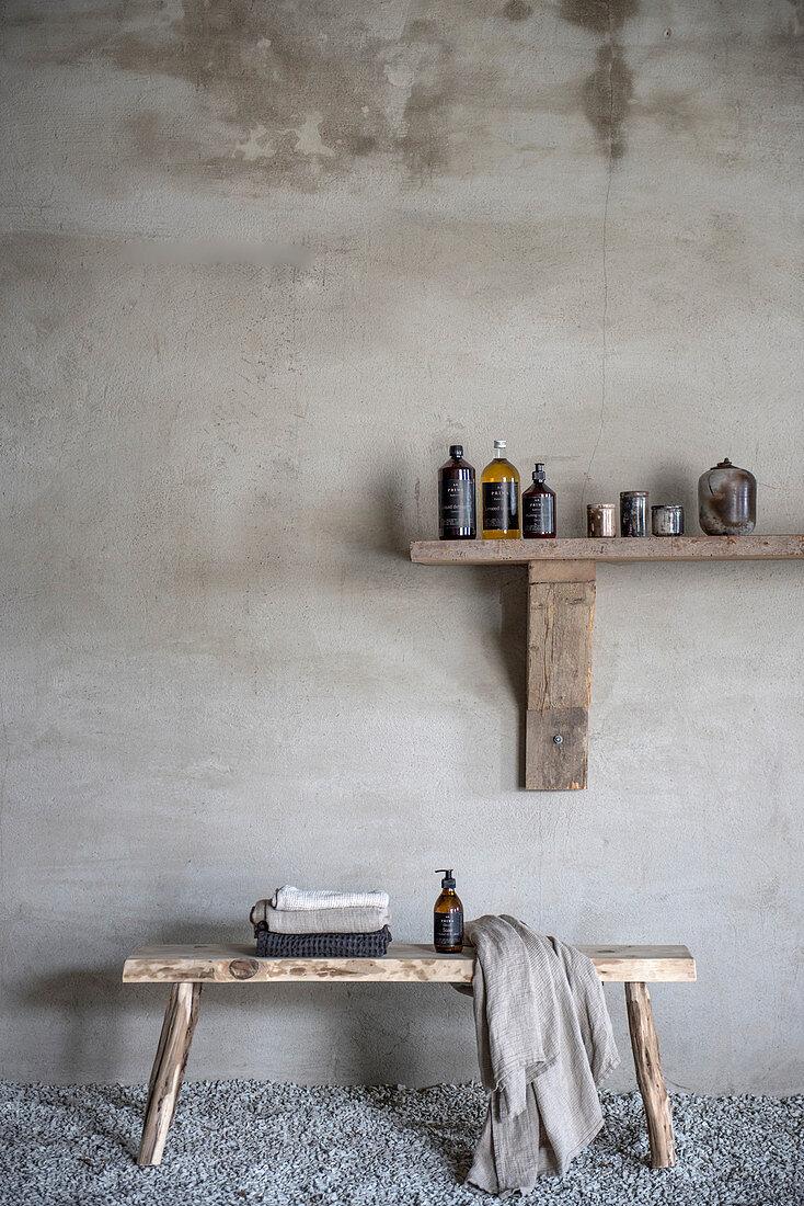 Bathroom utensils on wooden shelf above wooden bench