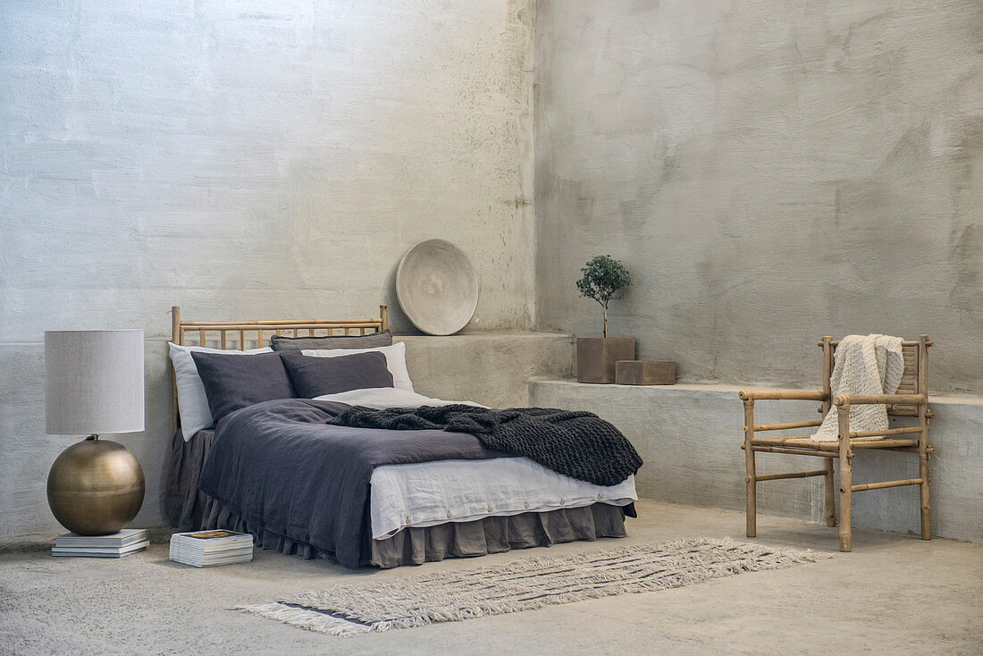Double bed, bamboo chair and large table lamp on floor in room with grey walls