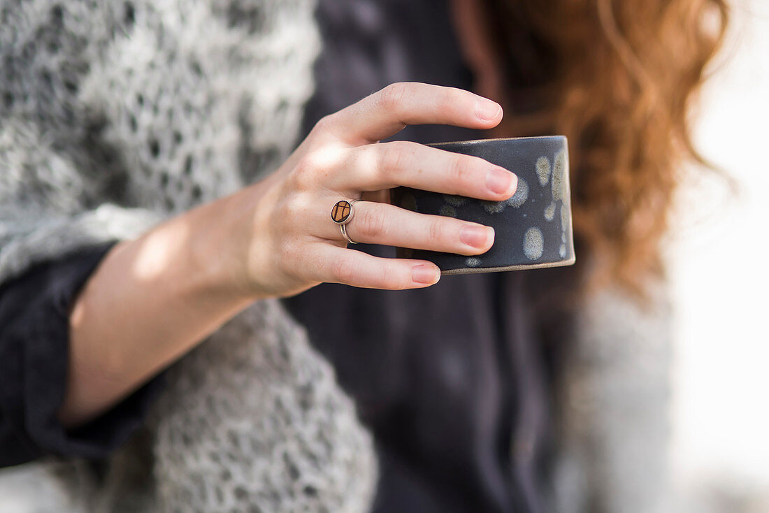 Hand of woman wearing ring and holding beaker