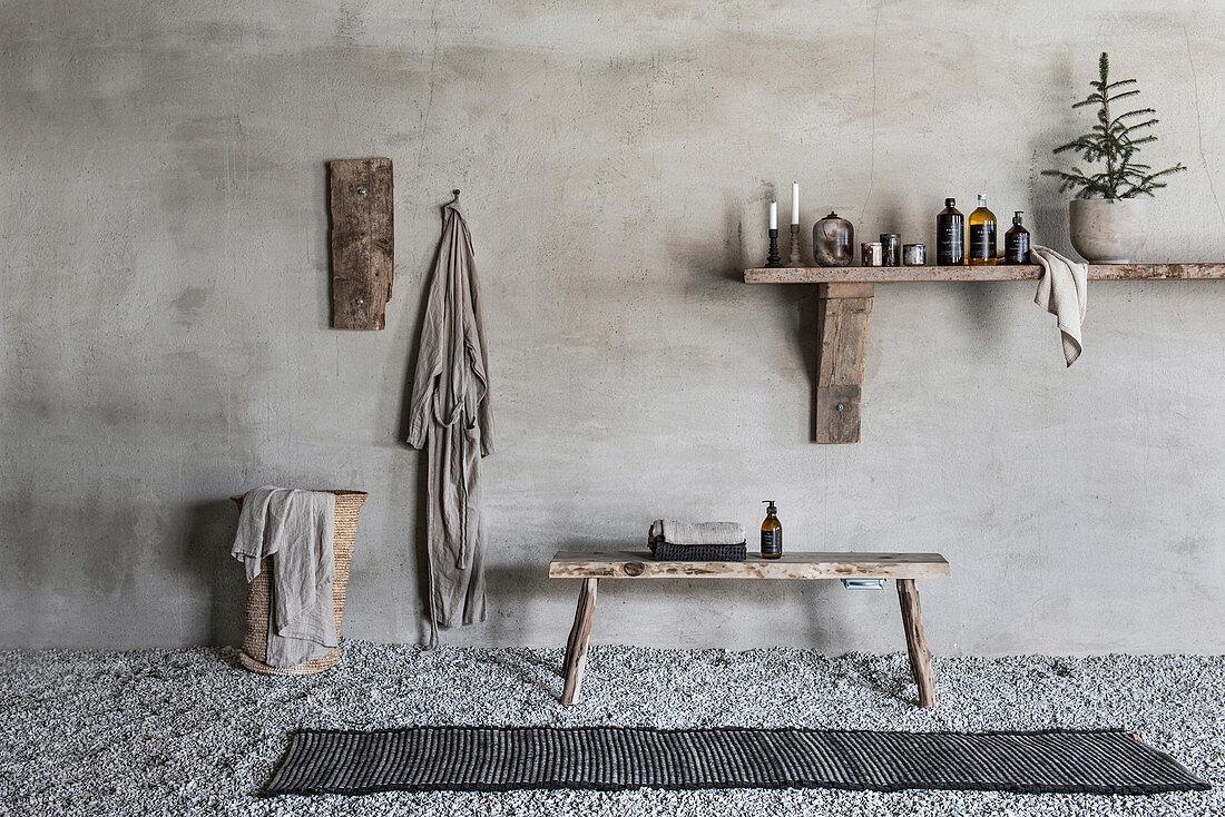 Bathroom utensils on wooden shelf, wooden bench, bathrobe and laundry basket