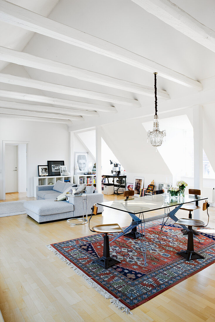 Swivel chairs at glass table in open-plan interior with exposed, white ceiling beams