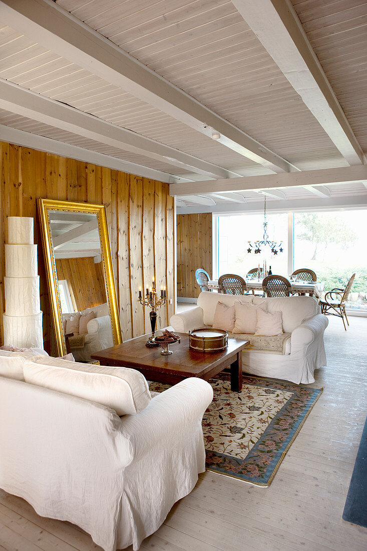 White loose-covered sofas and gilt-framed full-length mirror in country-house-style living room