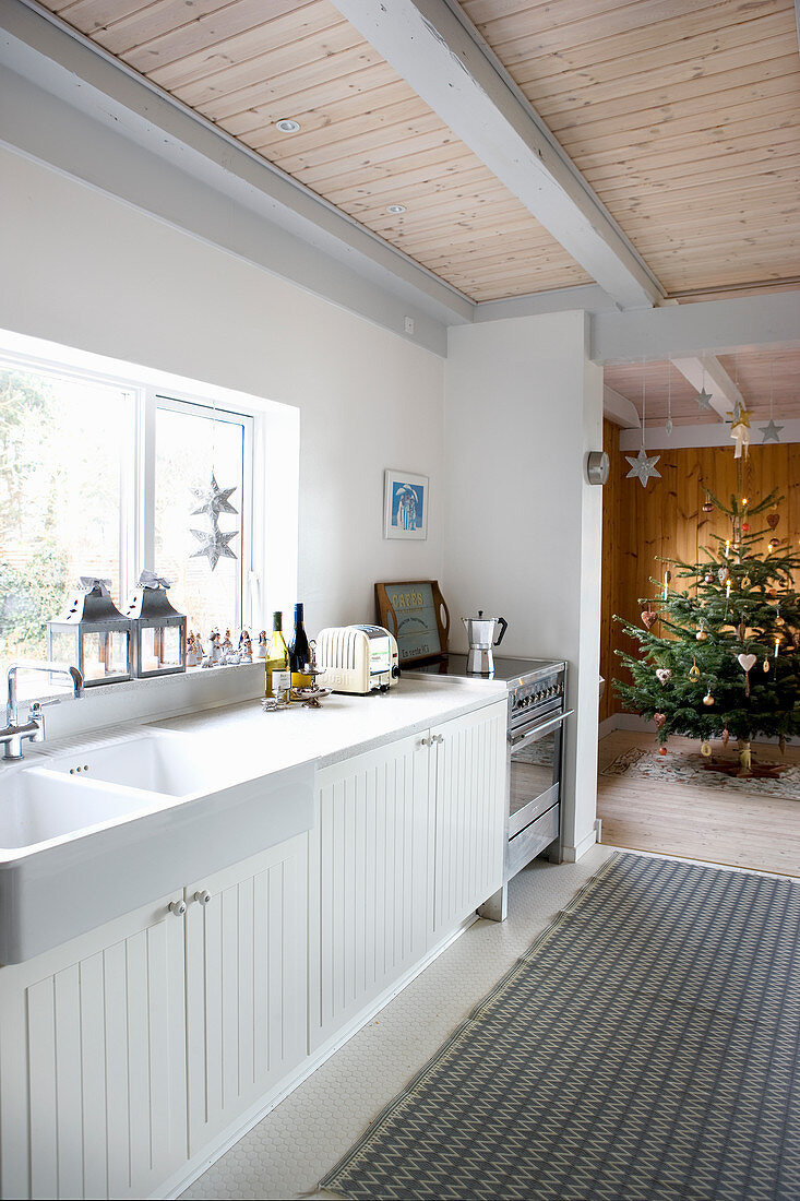 White country-house kitchen with open doorway leading into festively decorated Christmas tree