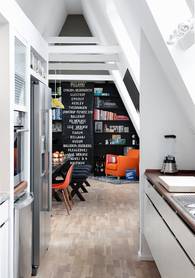 View from kitchen into dining room with black wall in attic apartment