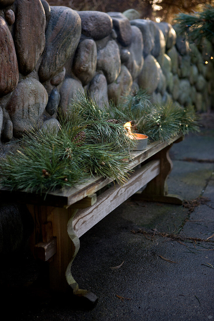 Wintry arrangement of conifer branches and candle lantern on wooden bench against stone wall