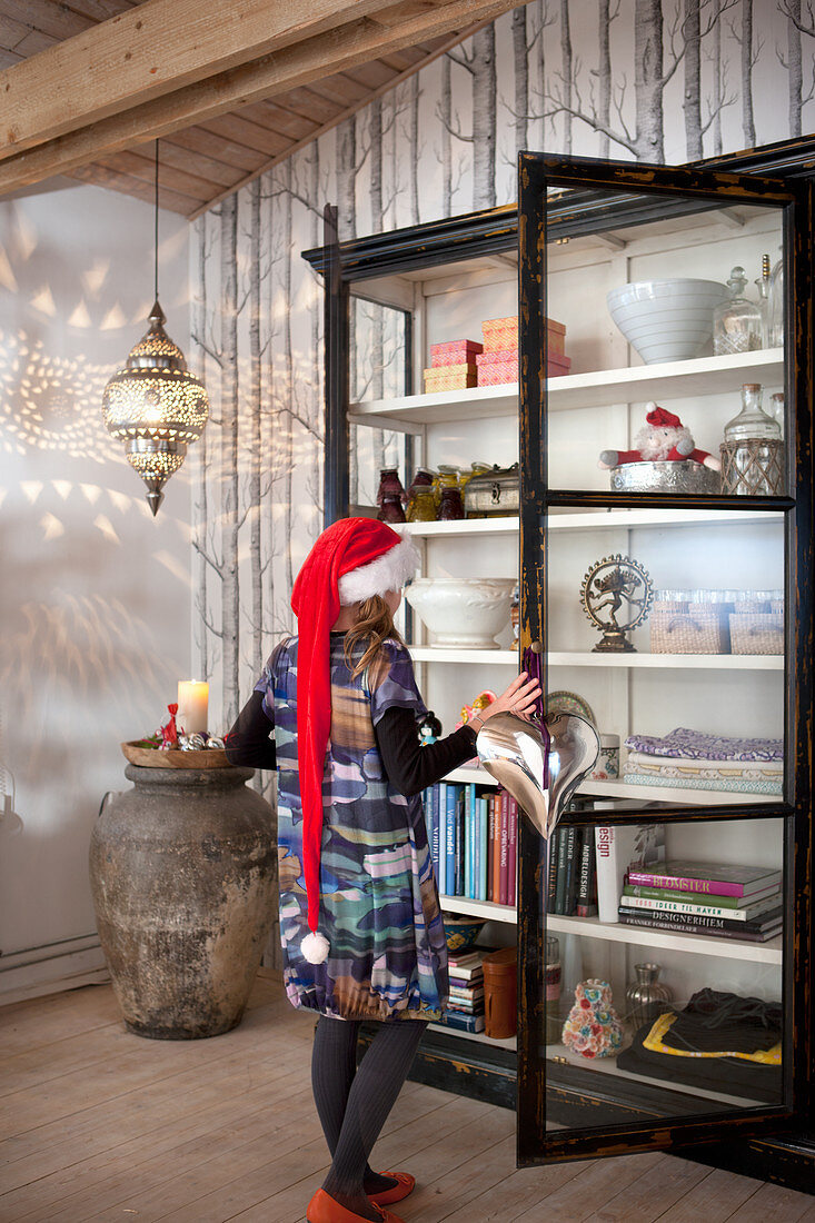 Child wearing Christmas hat in front of open display case