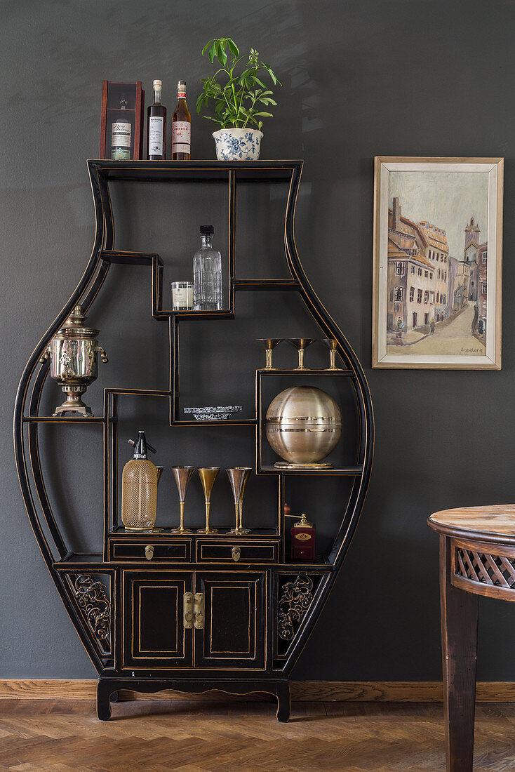 Black, vase-shaped shelving unit against dark grey wall in dining room