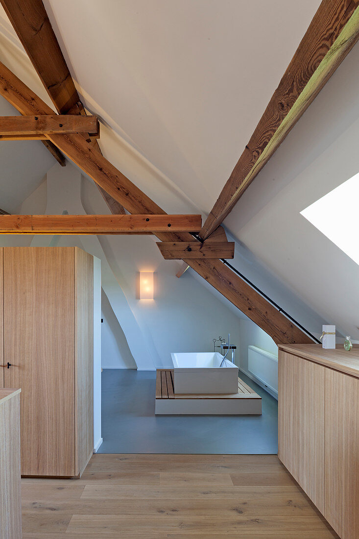 View into white, minimalist modern bathroom with wooden beams
