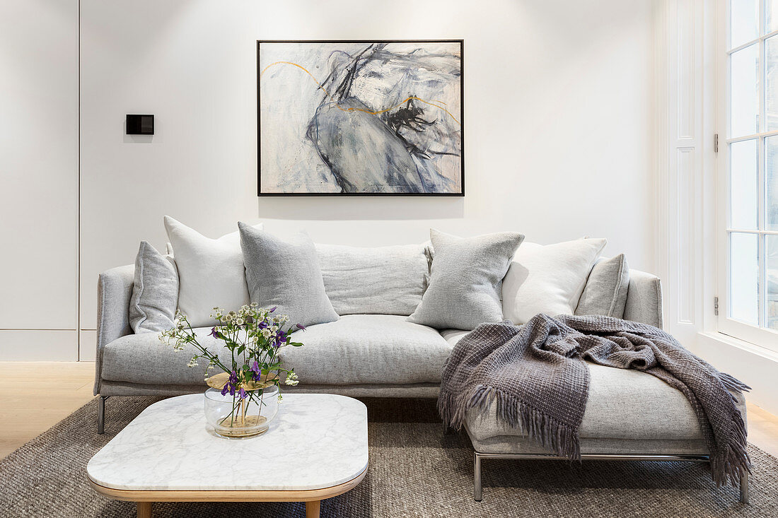 Grey modern sofa below abstract painting in living room