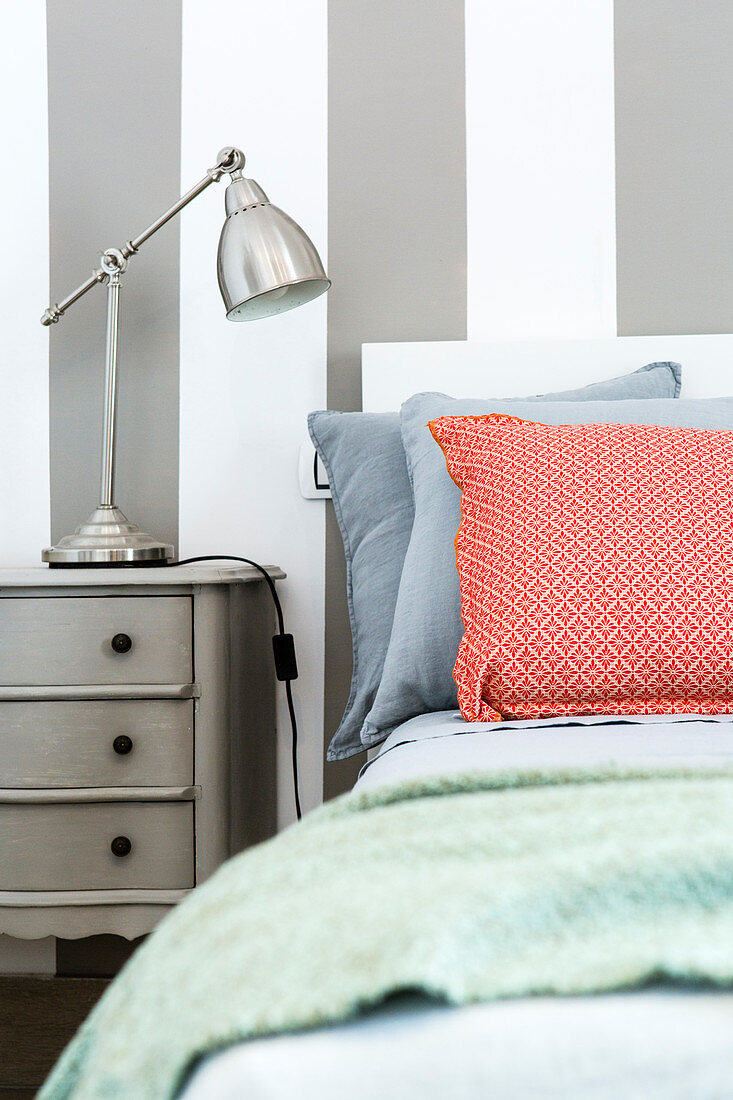 Red-patterned scatter cushion on bed against grey-and-white striped wall