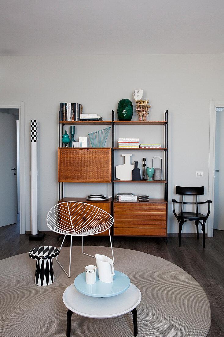 Retro Bücherregal, runder Teppich, Klassikerstuhl und Beistellitsche im Wohnzimmer