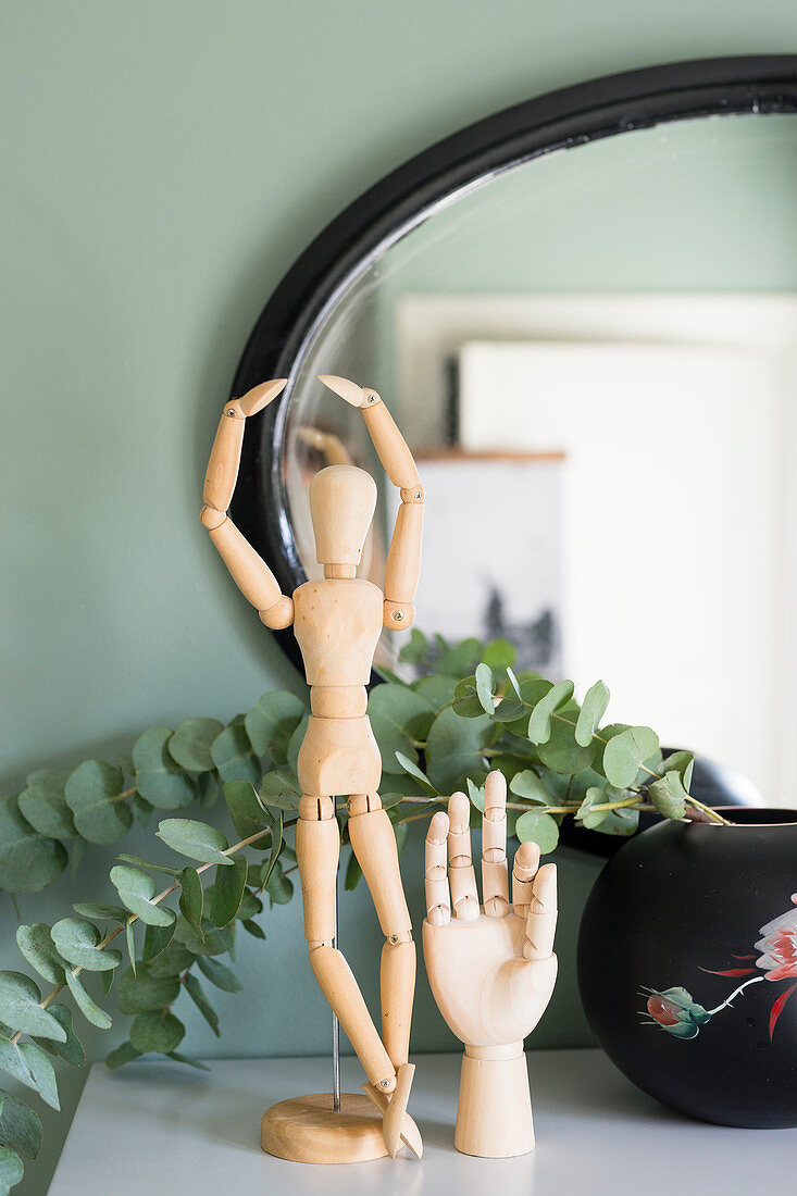 Artists' mannequin, model of hand and eucalyptus branches in front of mirror