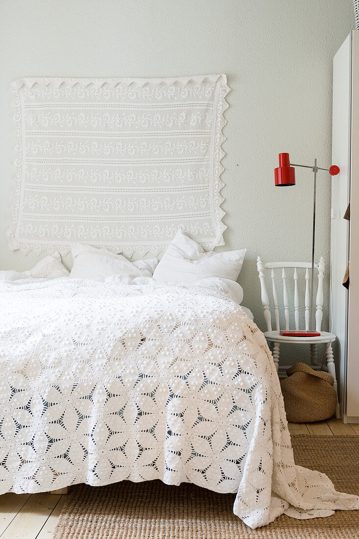 Lace cloth hung on wall above bed with romantic bedspread