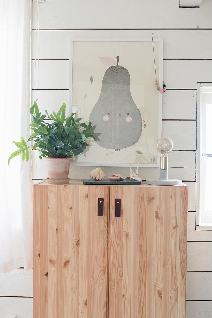 Cute picture of pear above wooden cabinet with leather strap handles