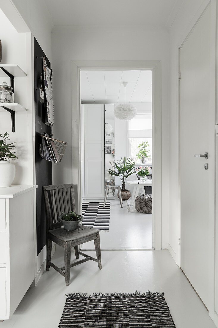 Old chair against black wall panel in white hallway