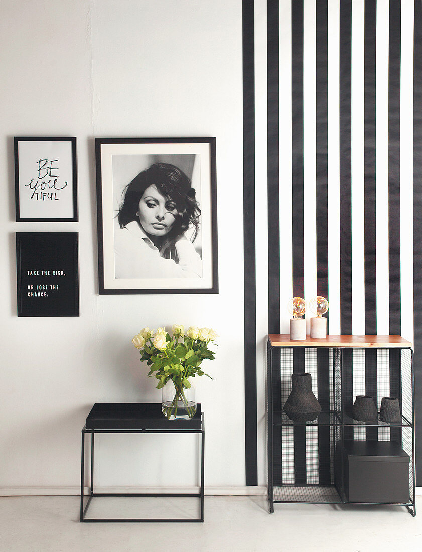 Side table and shelf against black-and-white wall with pictures on striped wallpaper