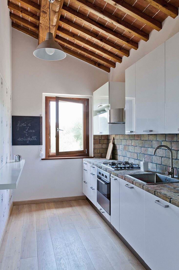 Kitchen with white cupboards and exposed wooden roof structure in Tuscan country house