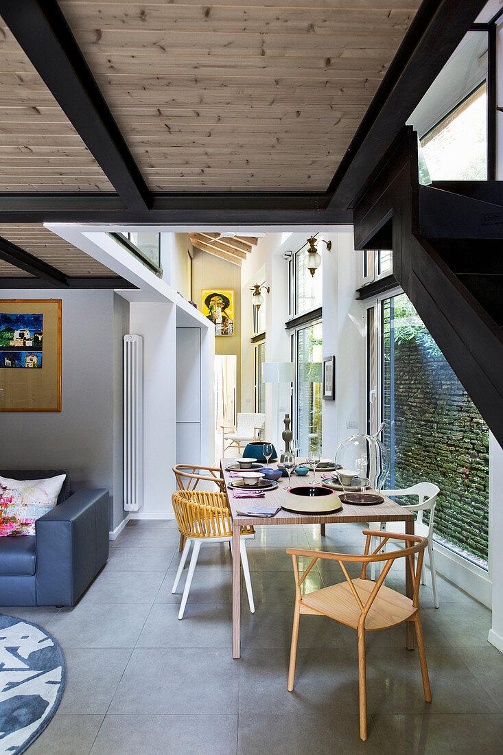 Loft-Wohnung mit deckenhohen Fensterfronten und Esstisch im Durchgangsbereich