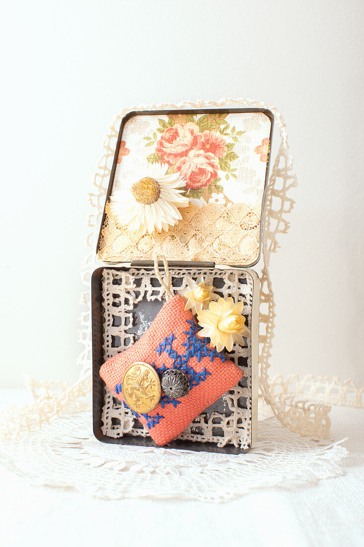 Old tin decorated with wallpaper, everlasting flowers, lace, pin cushion and buttons