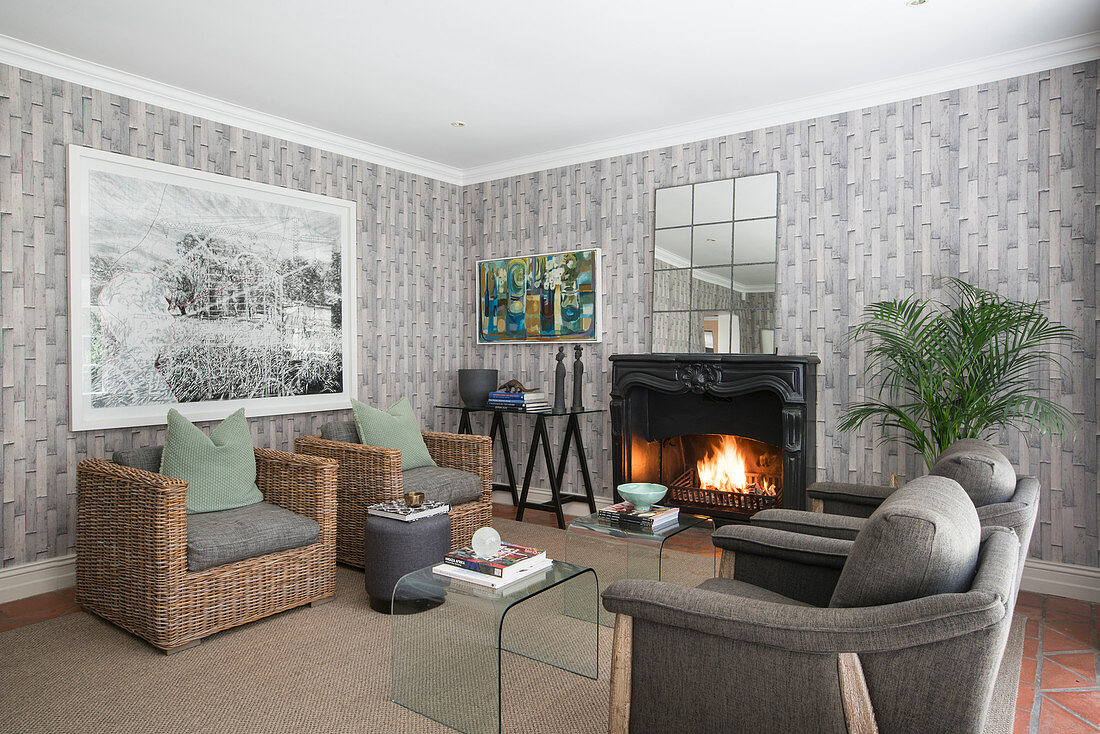 Rattan and upholstered armchairs grouped around open fireplace in living room with grey wallpaper