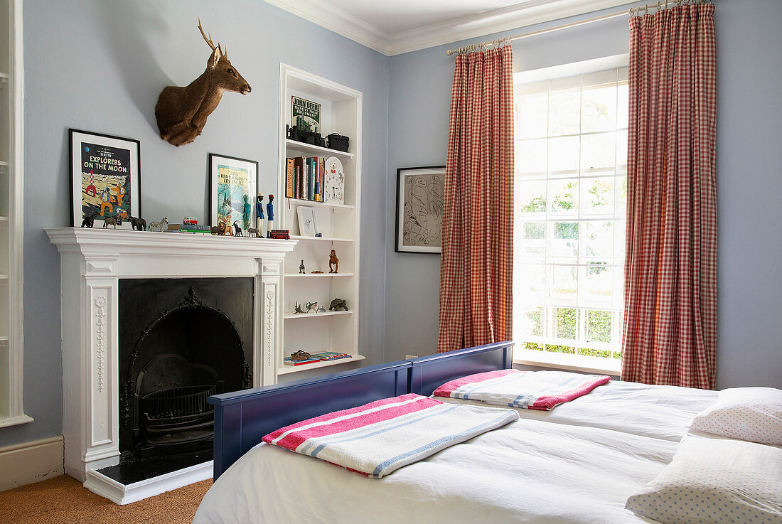 Hunting trophy above open fireplace in bedroom with lavender walls