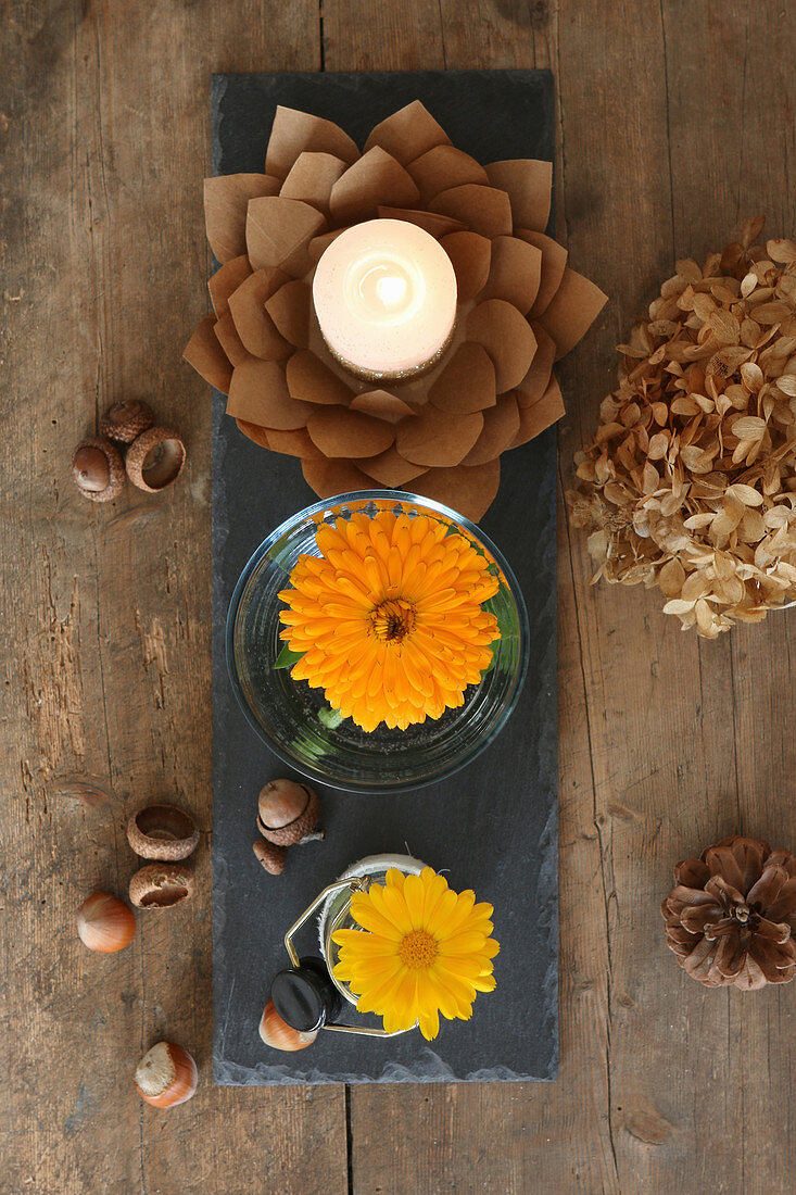 Autumnal arrangement of yellow pot marigolds in jars and paper-flower candle holders
