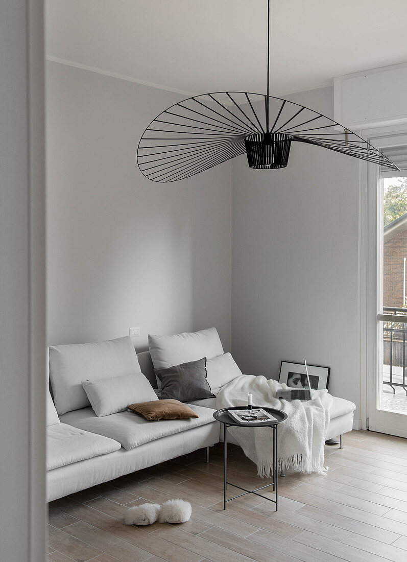 White couch with scatter cushions and black designer lamp in living room with pale grey walls