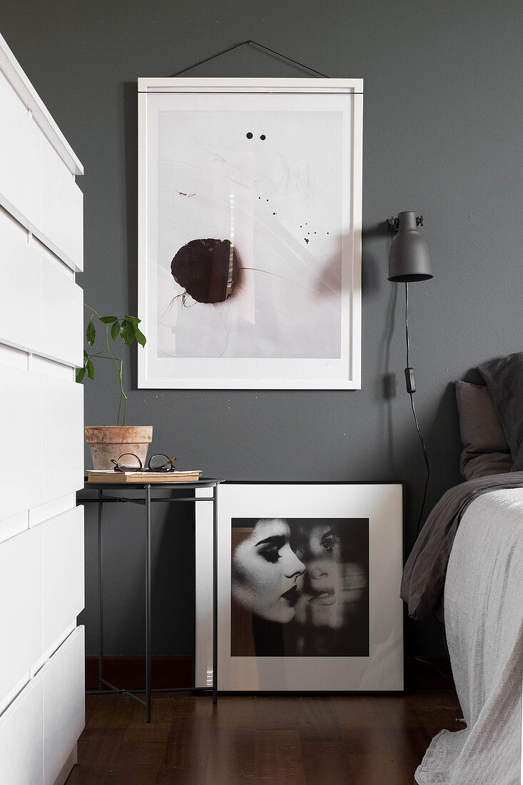 Modern artwork on grey wall above bedside table and black-and-white photograph in bedroom