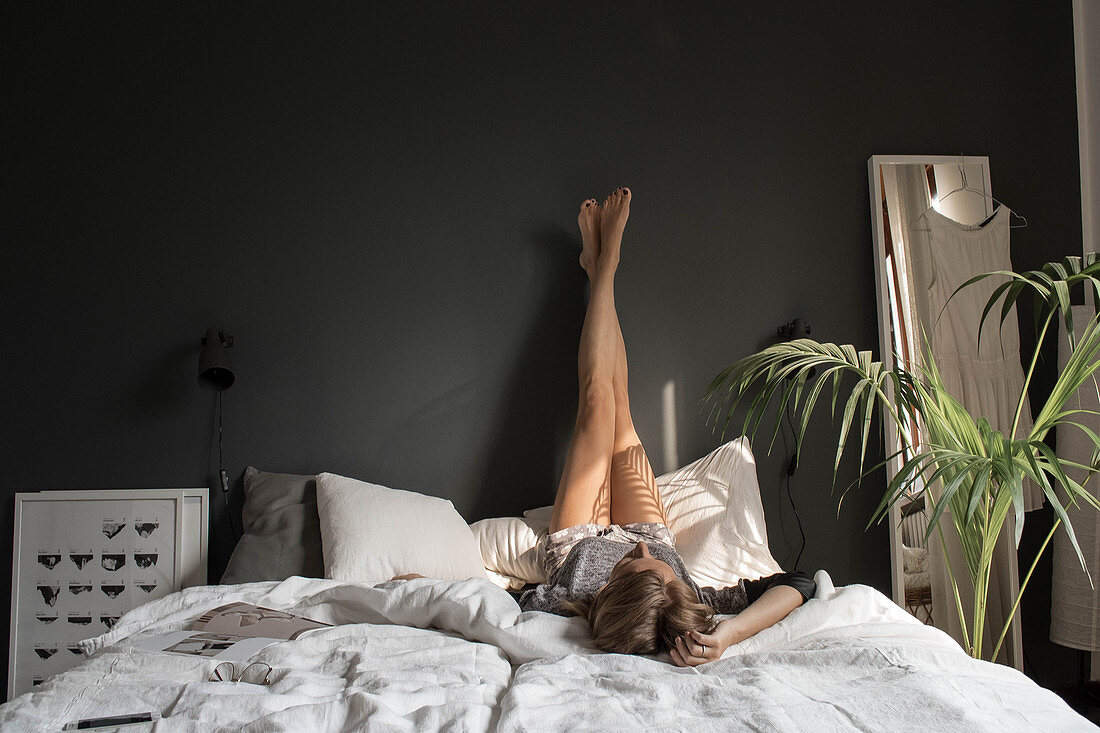Young woman lying on double bed with legs stretched up dark grey wall