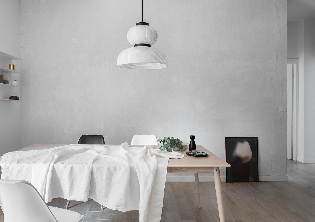 White tablecloth, carafe and eucalyptus branch on pale wooden table