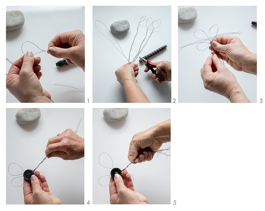 Hands bending wire to make flower with button centre