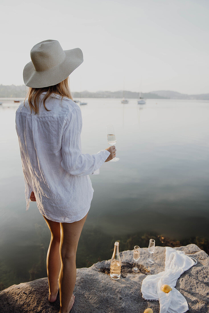 Woman wearing beach dress holding glass of sparkling wine on rocky lake shore